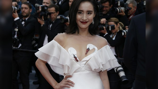 Seorang tamu Cannes Film Festival ini jelas mengetahui bagaimana menarik perhatian kamera. Ia menggunakan dress putih dengan aksesori tambahan di bagian dada. Bukan sembarang aksesori, tapi sepasang angsa yang menutupi dada. Sensor jenis baru. (REUTERS/Eric Gaillard)