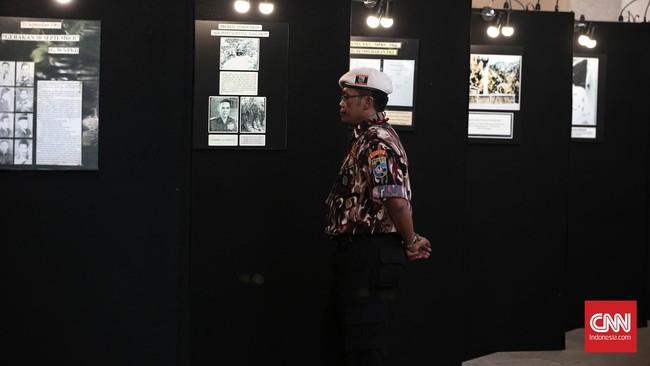 Seorang anggota ormas melihat-lihat foto di stan pameran pada acara Simposium Nasional 'Mengamankan Pancasila dari Kebangkitan PKI dan Ideologi Lain' yang berlangsung di Balai Kartini, Jakarta, Kamis (2/6). (CNN Indonesia/Andry Novelino)