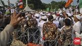 Massa Anti Partai Komunis Indonesia sempat membuat ricuh karena dihadang kawat duri dan beton saat berada di depan Istana Merdeka. (CNN Indonesia/Adhi Wicaksono).