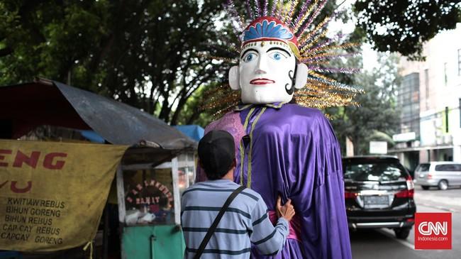 Seorang anggota pengamen ondel-ondel sedang memakaikan boneka ondel-ondel ke anggota lainnya yang bertugas mengenakannya.Profesi pemanggul Ondel-Ondel ini disebut Panjak.
