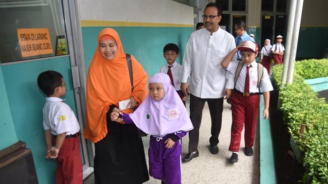 Wakil Gubernur Jawa Timur Saifullah Yusuf (kedua kanan) mengantarkan anaknya, M. Farellino Ramadhan (kanan), saat HPS di SD Al-Hikmah Surabaya, Senin (18/7). (ANTARA FOTO/M Risyal Hidayat)