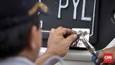 Petugas memasang kir mobil peserta saat tes uji SIM dan kir transportasi online di Jakarta, Senin 15 Agustus 2016. (CNN Indonesia/Adhi Wicaksono)