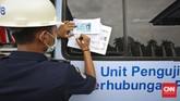 Petugas mengisi form penilaian mobil peserta saat tes uji SIM dan kir transportasi online di Jakarta, Senin 15 Agustus 2016. (CNN Indonesia/Adhi Wicaksono)
