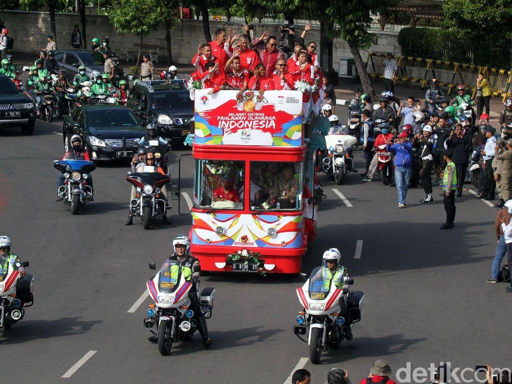 Tampak puluhan mobil dan sepeda motor mengiringi rombongan atlet.