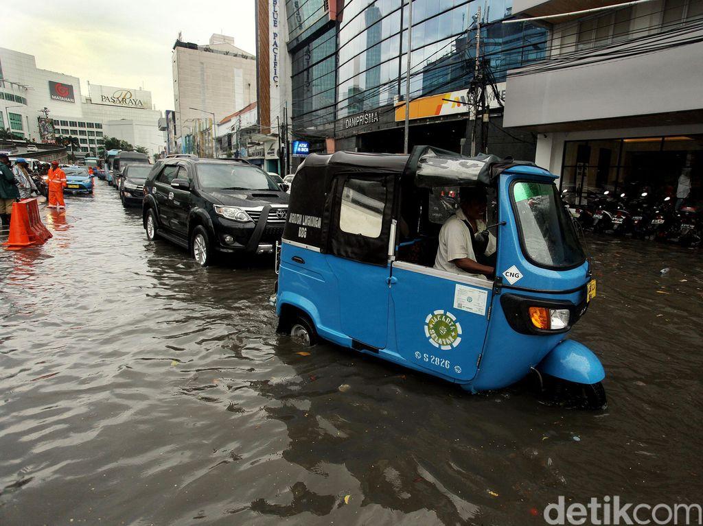 Sebuah bajaj menerobos banjir.