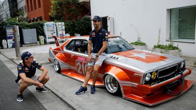 Dua pebalap tim Red Bull, Daniel Ricciardo (kanan) dan Max Verstappen (kiri) berpose bersama di depan mobil legendaris Jepang, Nissan Skyline buatan tahun 1979 yang telah dimodifikasi bentuk. (Reuters/Toru Hanai)