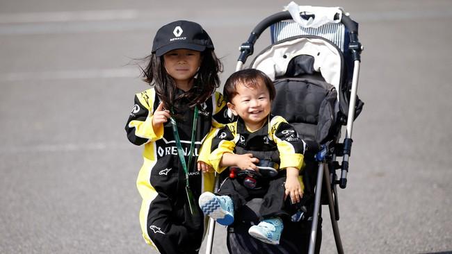 Dua bocah yang dibawa orang tuanya yang menggemari F1 berpose di arena paddock sirkuit Suzuka. (Reuters/Toru Hanai)