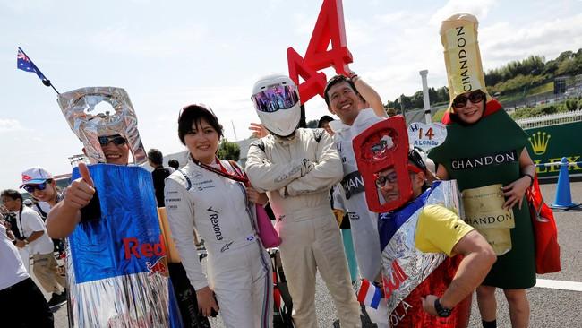 Para penggemar F1 berkumpul di sirkuit Suzuka, Jepang dengan kostum-kostum khas kreasi mereka. (Reuters/Toru Hanai)