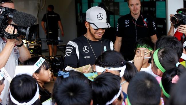 Meskipun kesal karena gagal finis pada seri grand prix di Malaysia pekan lalu, Pebalap Mercedes Lewis Hamilton tetap melemparkan senyum saat menerima permintaan tanda tangan dari bocah-bocah penggemar dirinya di sirkuit Suzuka. (Reuters/Toru Hanai)