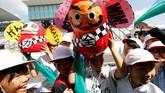 Anak-anak kecil setempat membawa boneka Daruma di pit lane. Boneka Daruma adalah boneka khas Jepang yang dipercaya dapat memberikan keberuntungan yang bagus. (Reuters/Toru Hanai)