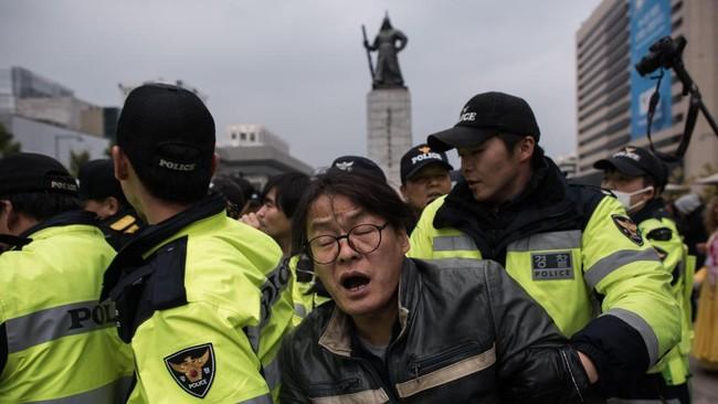 Choi, 60, ditahan polisi pada Kamis (3/11) atas dugaan berupaya mencampuri urusan negara dengan memanfaatkan kedekatannya dengan presiden. Ia juga dilaporkan memeras konglomerat lokal agar memberikan sumbangan bernilai jutaan dolar kepada lembaga non-profit yang dikelolanya, yang digunakan untuk kepentingan pribadi. (AFP Photo/Ed Jones)