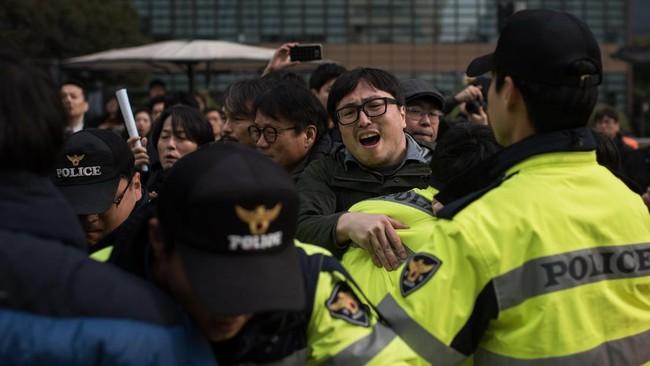 Akibat skandal ini, sekitar 1.200 warga Korea Selatan berunjuk rasa di Seoul sejak pekan lalu untuk menuntut pengunduran diri Presiden Park Geun-hye. Jajak pendapat Gallup menunjukkan tingkat kepercayaan masyarakat kepada Park merosot hingga 5 persen pada akhir pekan ini. (AFP Photo/ Ed Jones)