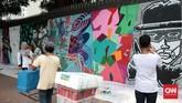 Pengunjung yang tak sengaja lewat dan menonton, pedagang asongan yang mangkal di sekitar area itu, menyaksikan aksi para seniman dengan antusias. Mereka kemudian berfoto selfie dengan latar belakang dinding yang kini penuh corak dan atraktif itu. (CNN Indonesia/Andry Novelino)