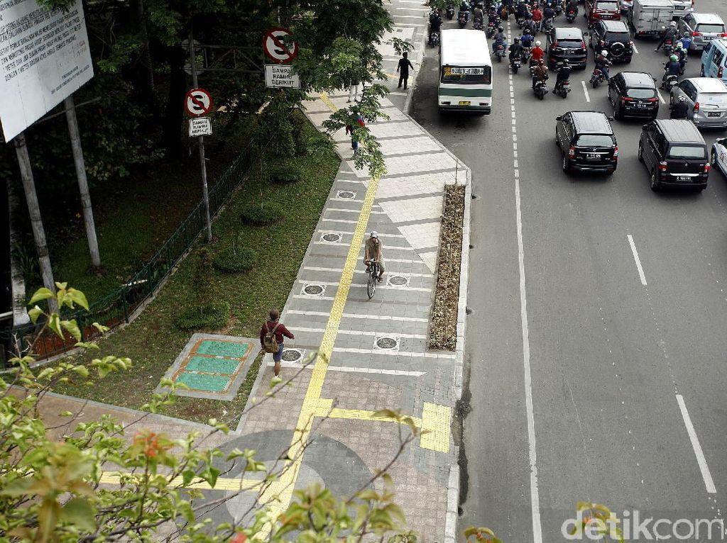 Beberapa warga melintas di trotoar Jalan Jati Baru.