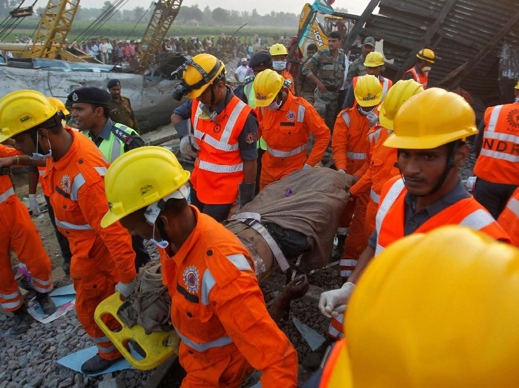 Para petugas nampak mengevakuasi korban. Kecelakaan ini menjadi tragedi kereta api terburuk di India sejak tahun 2005. Sebelas tahun lalu itu terjadi kecelakaan kereta yang terjun ke sungai dan menyebabkan sedikitnya 100 orang tewas.