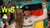 Nico Rosberg mendapatkan ucapan selamat dari sang istri, Vivian Sibold usai menjadi juara dunia F1 musim ini. (AFP PHOTO / KARIM SAHIB)