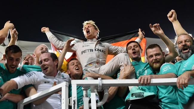 Nico Rosberg saat merayakan gelar bersama timnya. Bagi Rosberg, kemenangan ini adalah hasil manis setelah ia hanya mampu jadi runner up di musim 2014 dan 2015. (AFP PHOTO / Andrej ISAKOVIC)