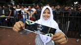 Seorang perempuan yang rela mengantri dengan bahagia menunjukkan tiket leg pertama semifinal Piala AFF yang berhasil ia beli. (ANTARA FOTO/Rivan Awal Lingga)