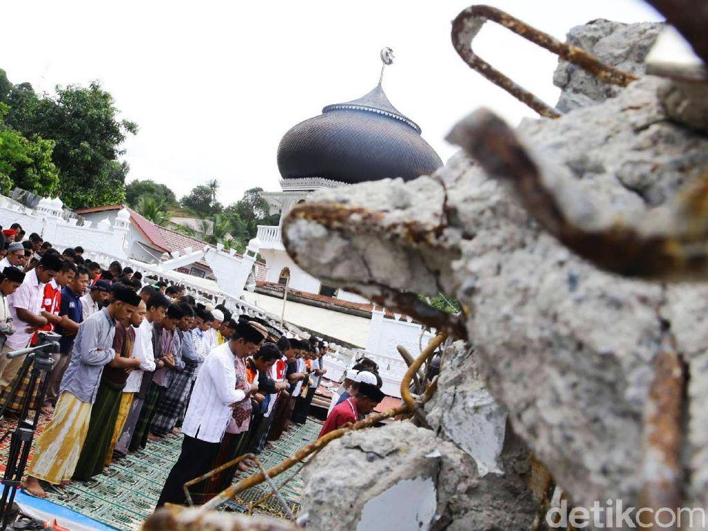 Warga saat menunaikan ibadah salat Jumat di sekitar reruntuhan masjid.