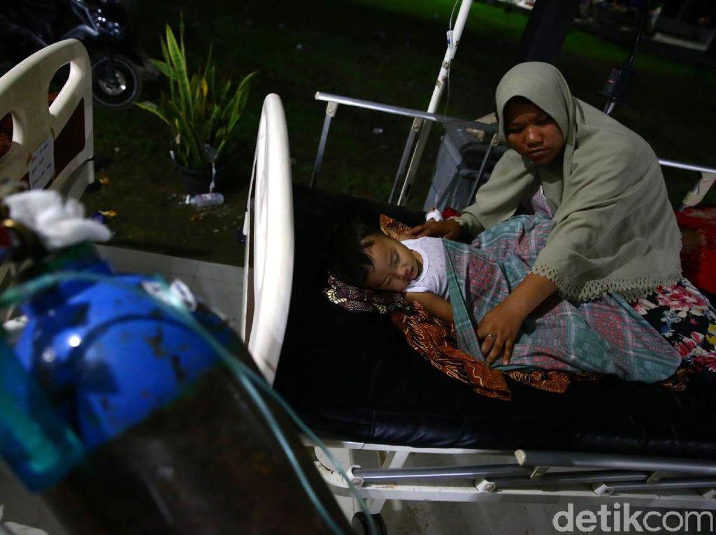 Seorang ibu merapikan selimut anaknya supaya tetap lelap dalam tidur.