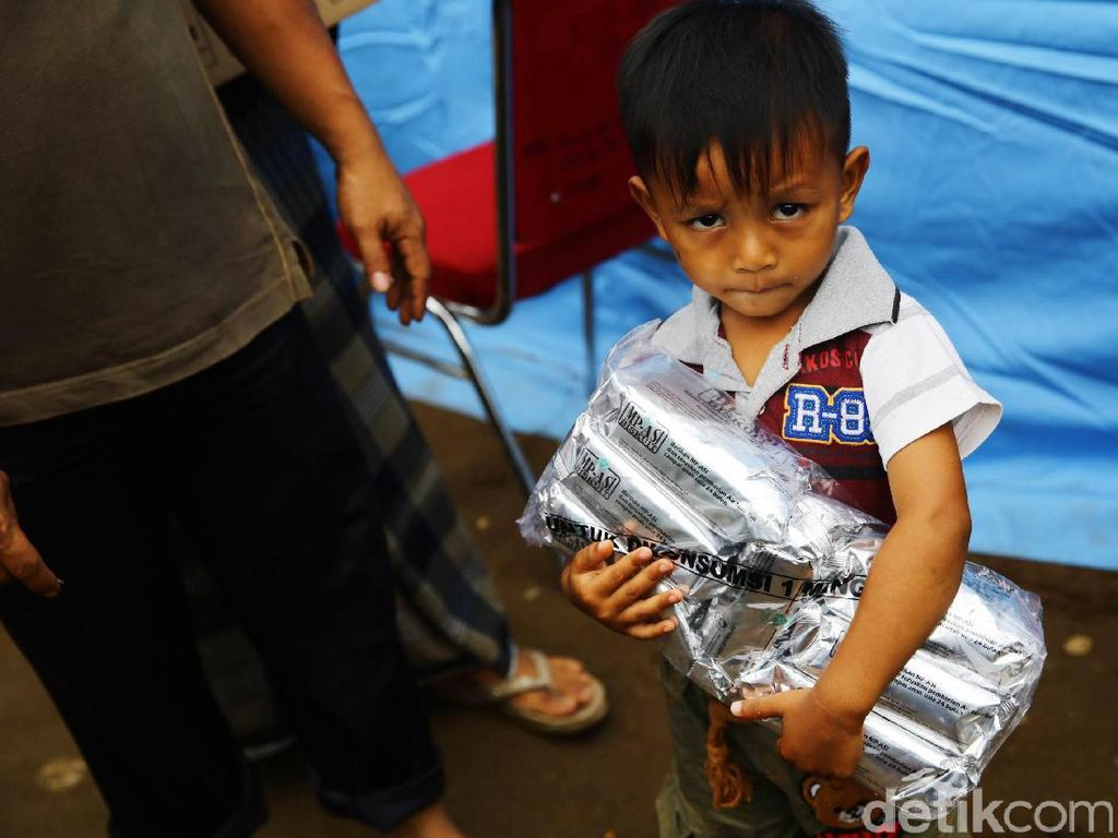 Seorang bocah memegang sekantung biskuit.