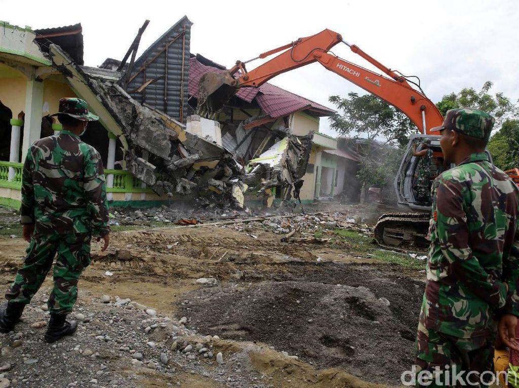 Ekskavator membongkar musala yang rusak akibat gempa.