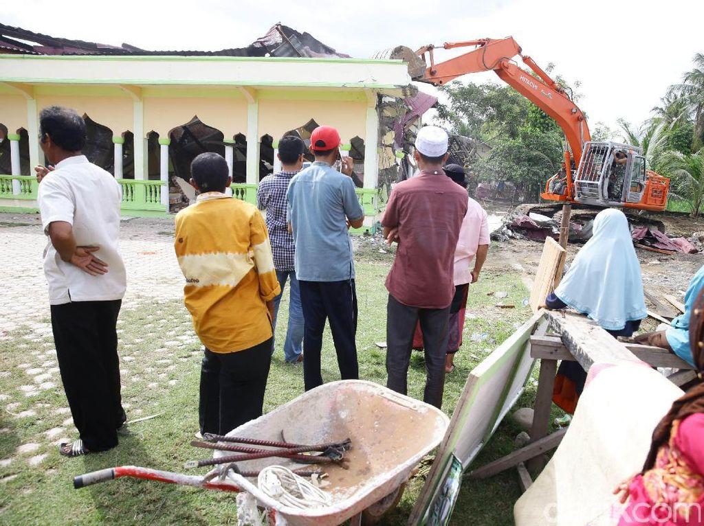 Warga menyaksikan pembongkaran musala yang rusak akibat gempa.