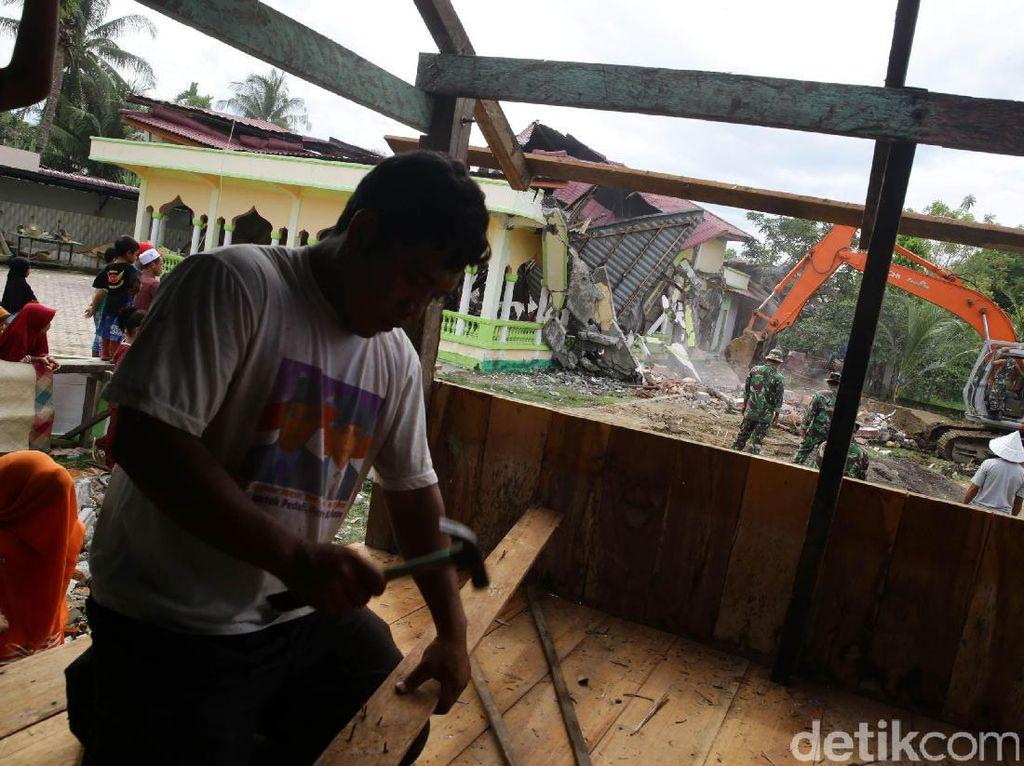 Musala darurat tersebut dibangun warga di halaman musala yang runtuh akibat gempa.