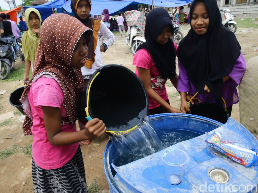 Sejumlah anak pengungsi tengah mengumpulkan air bersih di Desa Tijien Daboh, Pidie Jaya, Aceh, Minggu (11/12/2016).