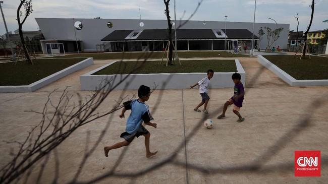 Tiga bocah bermain bola di RPTRA Kalijodo. Meski masih ada pengerjaan, pengunjung tetap diperbolehkan menghabiskan waktu di area yang telah dibuka, seperti lapangan bola di bagian depan. (CNN Indonesia/Safir Makki)