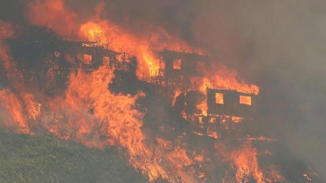 Kobaran api melalap setidaknya 100 rumah di Kota Valparaiso, Chile, pada Senin (2/1) malam. Sebanyak 19 orang terluka akibat insiden ini. (Reuters/Rodrigo Garrido)
