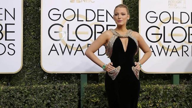 Hot mama Blake Lively terlihat seksi dengan balutan gaun hitam beludru dengan tambahan aksen emas di bagian kantong, leher, dan lengan. Gaun body contour ini juga membentuk lekuk tubuhnya yang seksi. (REUTERS/Mike Blake)