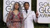 Para selebriti pria di Golden Globes 2017 biasanya memakai setelan jas hitam. Namun Pharrell Williams memilih menggunakan warna lain dalam setelan jasnya. Dia memilih jas panjang berwarna putih bermotif. Dia melengkapinya dengan rantai sisi dan dasi hitam.(REUTERS/Mike Blake)