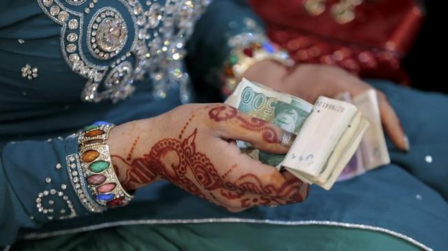 Sebagai imbalan karena sudah datang, para tamu diberikan 'uang ongkos' sesaat sebelum pulang. (REUTERS/Caren Firouz)