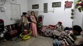 Dalam menyiapkan pesta, para transgender di Pakistan ini saling tolong menolong. Seperti yang dilakukan Bubbly, ia membantu persiapan pesta Shakeela mengenakan gaun tercantik untuk pesta itu. (REUTERS/Caren Firouz)