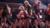 Penampilan Lady Gaga juga patut diingat. Tampil bersama Metallica, salah satu mikrofon mereka ternyata mati. Alhasil, Gaga harus berbagi mikrofon. Ia juga begitu lincah berlarian ke sana kemari, bahkan menjatuhkan tubuhnya ke kerumunan penonton. (REUTERS/Lucy Nicholson)