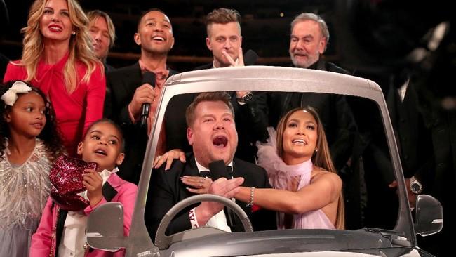 Bukan James Corden namanya jika tak bisa membuat suasana semakin kocak. Ia mendadak datang dengan cardboard Carpool Karaoke, acara yang dipandunya. Ia lalu duduk di samping Jennifer Lopez dan mengajak musisi lain bergabung 'masuk mobil,' menyanyi Sweet Caroline. (Christopher Polk/Getty Images for NARAS/AFP)