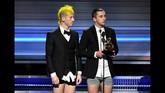 Tak lama, ada kejadian yang tak kalah menghebohkan. Twenty One Pilots yang memenangi Best Pop Duo/Group Performance, naik ke atas panggung sembari membuka celana mereka. Alhasil, mereka hanya mengenakan kemeja putih, jas, celana boxer, dan sepatu. (Kevin Winter/Getty Images for NARAS/AFP)
