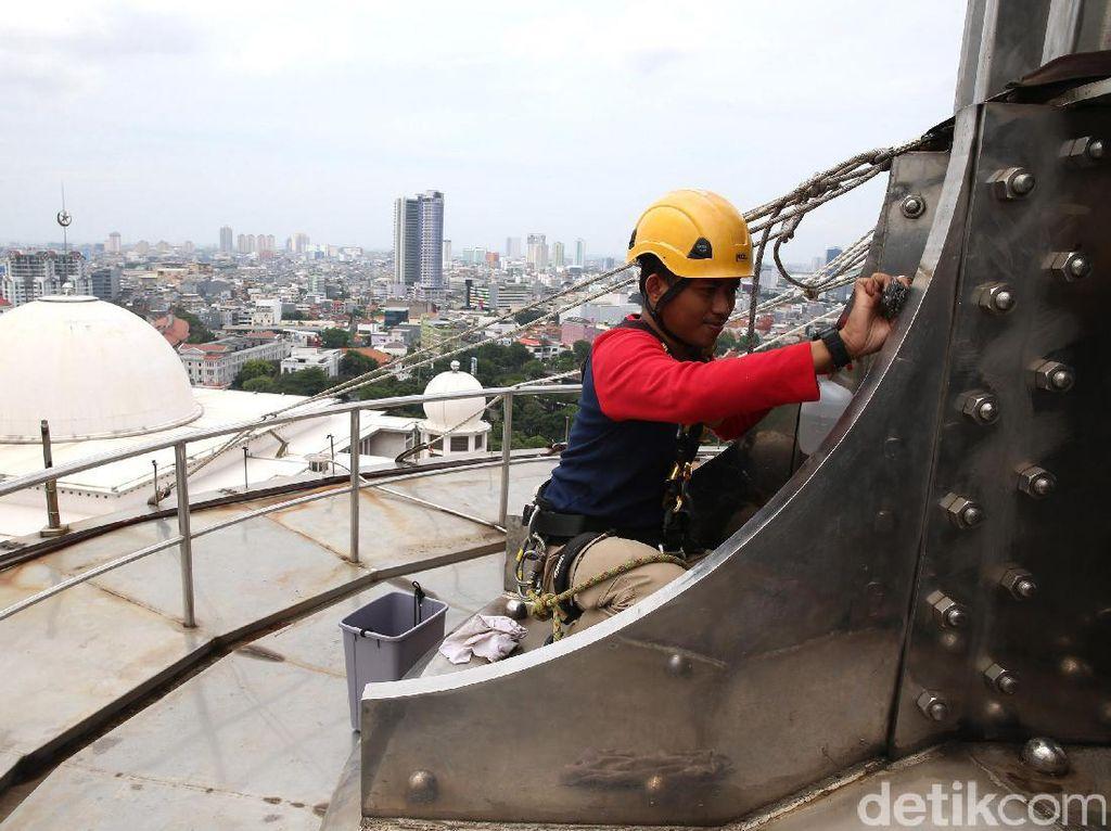 Seorang relawan membersihkan bagian puncak menara.