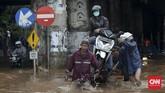 Tak hanya sepeda motor yang diangkut ke gerobak, pengendara pun ikut diangkut menembus banjir yang tak dapat dilalui kendaraan di bawah ruas Jalan Tol Bintara, Bekasi, Selasa (21/2). Baik pengendara motor maupun yang menarik gerobak harus berhati-hari karena banjir yang menerjang membawa arus. (CNN Indonesia/Safir Makki)