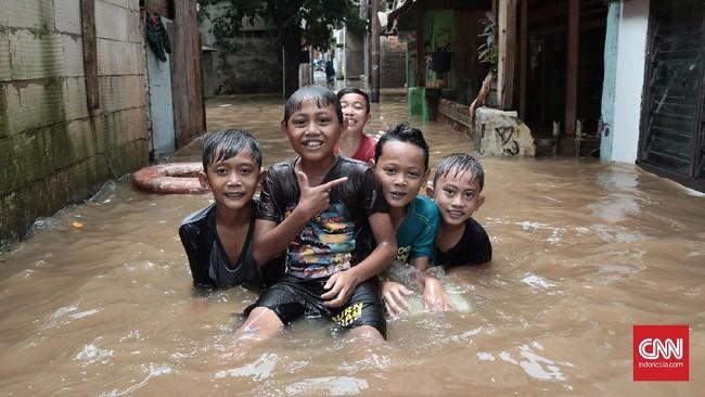 Anak-anak terlihat begitu menikmati bermain air kala banjir melanda perkampungan Rawajati, Jakarta Selatan, Selasa (21/2). Banjir yang merendam kawasan ini sejak pagi dan tak segera surut harus mendapat perhatian serius mengingat banyaknya anak-anak yang terkena dampak banjir. (CNN Indonesia/Andry Novelino)
