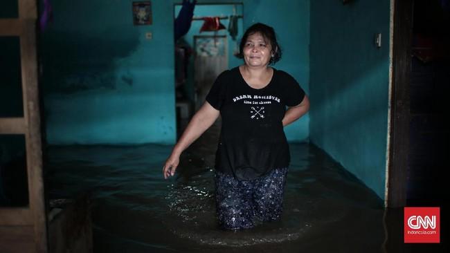 Seorang perempuan yang rumahnya terendam banjir di Jalan Bina Warga kawasan Rawajati, Jakarta Selatan, terendam banjir sejak Selasa (21/2) pagi. Ketinggian air di wilayah ini mencapai ketinggian hingga satu meter lebih. Warga membutuhkan penanganan segera. (CNN Indonesia/Andry Novelino)