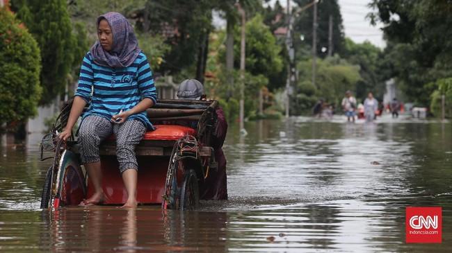 Keberadaan becak dimanfaatkan oleh warga yang wilayahnya dilanda banjir di kawasan Perumahan Pulo Permatasari, Bekasi Selatan, Selasa (21/2). Dengan adanya kendaraan roda tiga semacam ini sangat membantu warga yang butuh bantuan untuk bisa melewati lokasi banjir. (CNN Indonesia/Safir Makki)