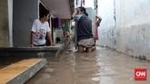 Warga di Jalan Bina Warga kawasan Rawajati, Jakarta Selatan, terutama kaum laki-laki yang bagian dalam rumahnya terendam banjir sejak Selasa (21/2) pagi, mengangkut barang-barang yang cukup berat agar tak terkena air. Mereka bergotong royong berusaha mengamankan barang berharga ke tempat yang lebih tinggi. (CNN Indonesia/Andry Novelino)