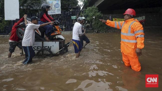 Sejumlah gerobak dikerahkan untuk membawa para pengendara motor untuk bisa menembus banjir yang tak dapat dilalui kendaraan di bawah ruas Jalan Tol Bintara, Bekasi, Selasa (21/2). Banyak warga yang merasa terbantu dengan adanya jasa gerobak-gerobak karena tak membuat pengendara memutar arah. (CNN Indonesia/Safir Makki)
