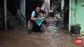 Tak hanya anak-anak, kaum perempuan di kawasan Jalan Bina Warga, Rawajati, Jakarta Selatan, yang terkena banjir hingga satu meter lebih sejak Selasa (21/2) pagi, terpaksa digendong karena tingginya air dan cukup derasnya arus. Kaum perempuan dan anak-anak diungsikan ke tempat aman yang tak terkena banjir. (CNN Indonesia/Andry Novelino)