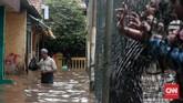 Seorang bapak tampak membawa barang yang dimasukan ke dalam plastik di wilayah Jalan Bina Warga, Rawajati, Jakarta Selatan, yang terkena banjir hingga satu meter lebih sejak Selasa (21/2) pagi. Kawasan ini kerap menjadi langganan banjir akibat meluapnya Kali Ciliwung saat hujan deras. (CNN Indonesia/Andry Novelino)