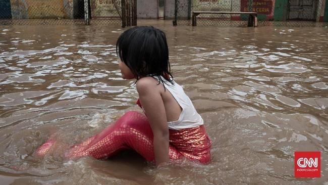 Di tengah kesulitan warga karena banjir, seorang anak perempuan yang mengenakan kostum ikan duyung, menikmati bermain air. Banjir di kawasan Jalan Bina Warga Rawajati, Jakarta Selatan, terjadi sejak Selasa (21/2) pagi. Ketinggian air di beberapa titik mencapai satu meter lebih. (CNN Indonesia/Andry Novelino)