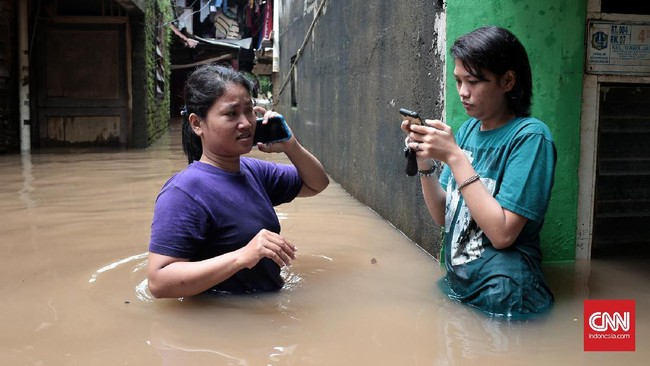 Warga di Jalan Bina Warga kawasan Rawajati, Jakarta Selatan, yang terkena banjir hingga satu meter lebih sejak Selasa (21/2) pagi, tampak berkomunikasi dengan telepon selulernya. Mereka banyak yang memberi kabar kepada sanak saudaranya mengenai musibah banjir yang dialaminya. (CNN Indonesia/Andry Novelino)