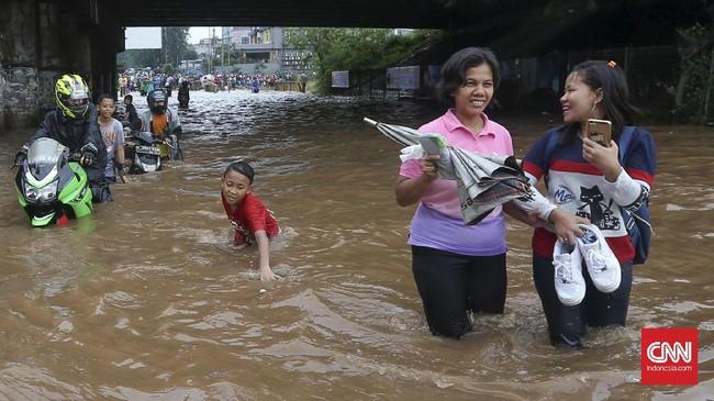 Selain beberapa pengendara sepeda motor yang nekat menembus banjir tanpa gerobak, sejumlah warga juga memaksakan diri menerjang banjir di bawah ruas Jalan Tol Bintara, Bekasi, Selasa (21/2). Banjir di kawasan ini sangat mengganggu aktivitas warga yang hendak melintas. (CNN Indonesia/Safir Makki)